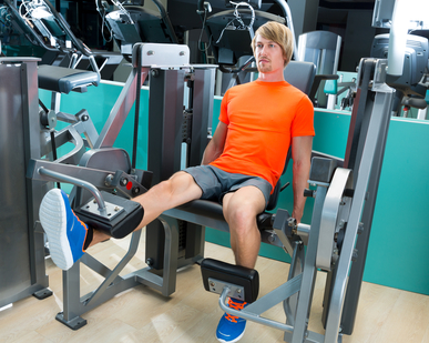 Gym blond man leg extension cuadriceps exercise workout at indoor